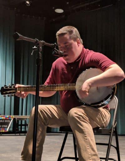 A man plays banjo in the talent show